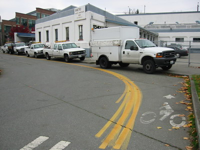 County vehicles park in bike lane